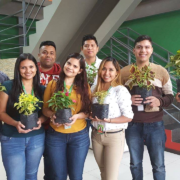 El Salvador Focus employees holding plants for an Earth Day celebration.